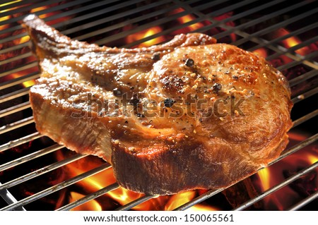 Grilled pork chop on flaming grill. - stock photo