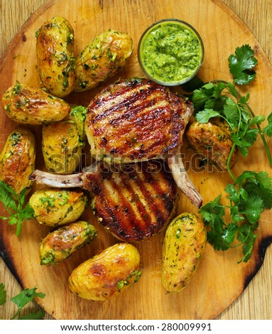 Grilled pork chop on the bone with spicy potatoes. Selective focus. - stock photo