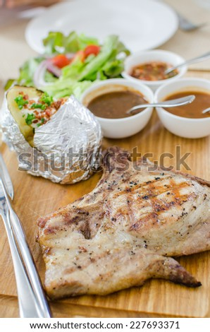 Grilled pork chop steak set with vegetables and sauce - stock photo
