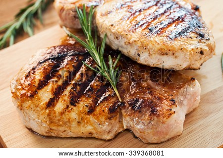 grilled pork chop with rosemary leaf on wooden board - stock photo