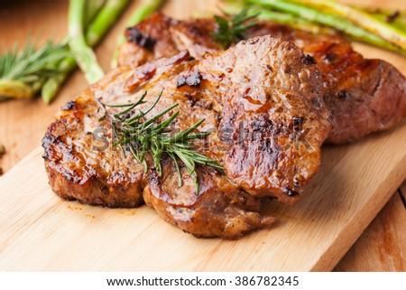 grilled pork chop with rosemary on wooden board - stock photo
