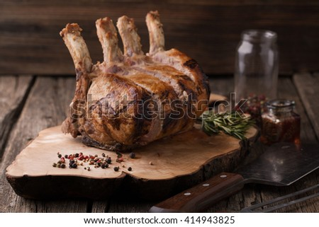 Grilled pork chop with spices, rosemary on a wooden background - stock photo