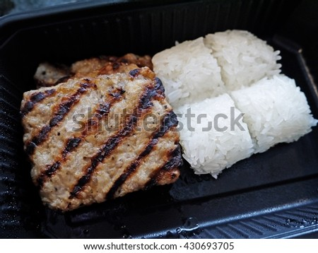 Grilled pork chop with sticky rice in black plastic box. Pork barbecue. Grilled steaks. Ready to eat or ready to go. Lunch set for camping. - stock photo