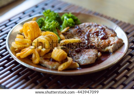 Grilled pork chops with curly fries and steamed broccoli - stock photo