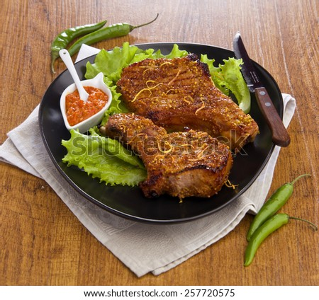 grilled pork chops with mustard sauce pepper lettuce on a black plate, wooden table - stock photo