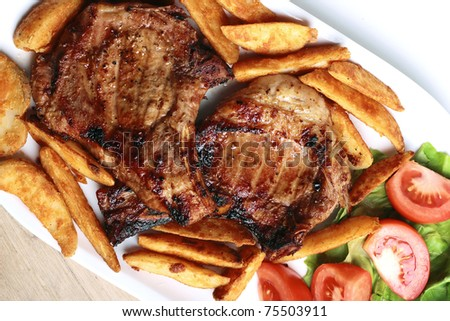 Grilled Pork Chops with Potatoes and Veggies - stock photo
