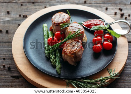 Grilled pork dish with fresh vegetables. Food photography of grilled pork medallions with herbs and spices. Tasty cook meat with  vegetables on dark wooden background.  - stock photo