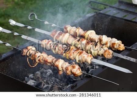 Grilled pork kebab on skewers, cooking process - stock photo