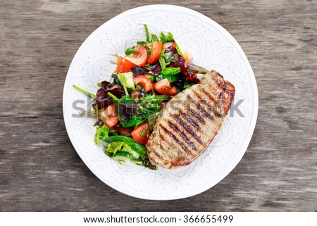 Grilled pork meat and vegetables on plate - stock photo