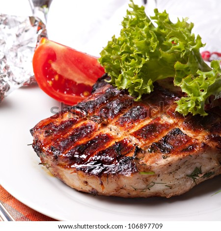 Grilled pork meat on plate with green salad - stock photo