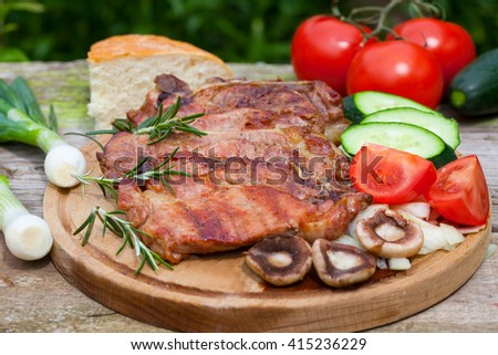 Grilled pork meat with mushrooms and fresh vegetable salad on wooden board - stock photo