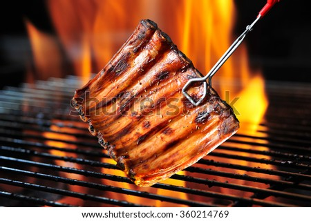 Grilled pork ribs on the flaming grill - stock photo
