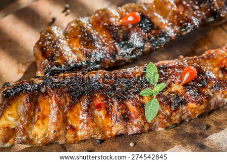 Grilled pork ribs on the wooden board - stock photo