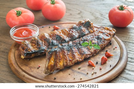 Grilled pork ribs with tomatoes on the wooden board - stock photo