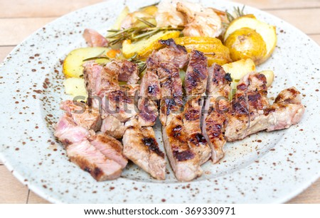 Grilled pork steak and baked potatoes - stock photo