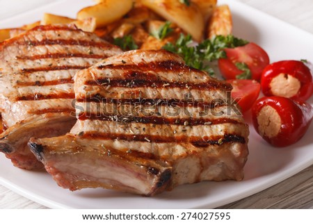 Grilled pork steak with potatoes and vegetables on a plate macro. horizontal