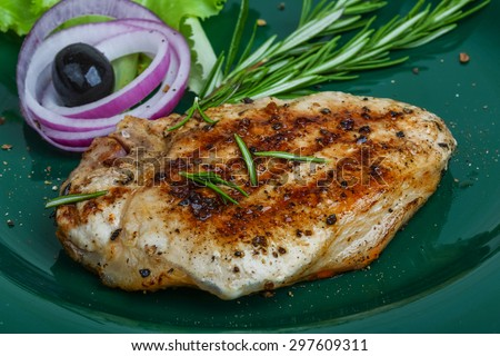 Grilled pork steak with rosemary on the wood background