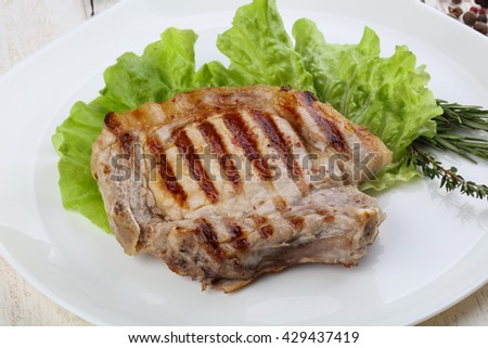 Grilled pork steak with salad leaves and pepper