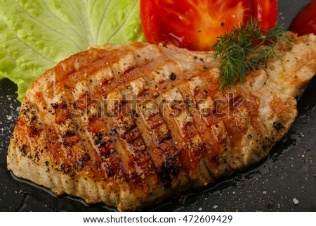 Grilled pork steak with salad leaves and tomato