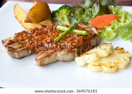 Grilled pork steaks, baked potatoes and vegetables. - stock photo