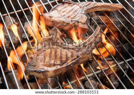 Grilled pork steaks over flames on the grill - stock photo