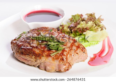 Grilled pork steaks with raspberry sauce, rosemary and leaf of lettuce - stock photo