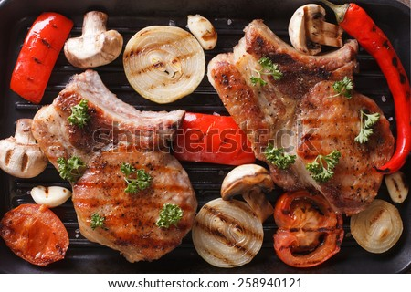 Grilled pork with mushrooms and vegetables on grill macro. horizontal view from above