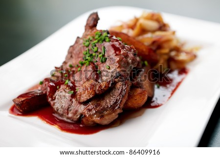 Grilled pork with spicy salad and baked potato - stock photo