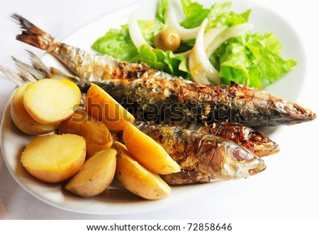 Grilled portugal sardine fish served with green salad and potatoes - stock photo