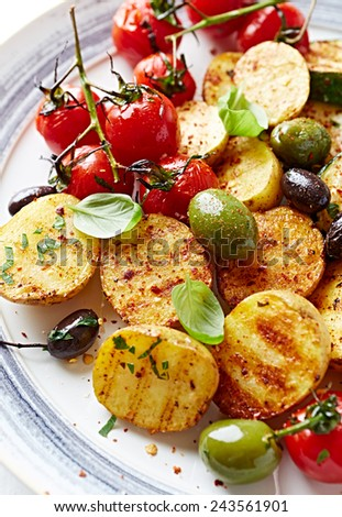 Grilled potatoes and cherry tomatoes with olives  - stock photo