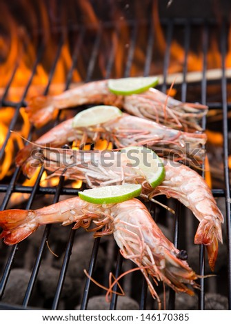 Grilled prawns on flaming grill. - stock photo