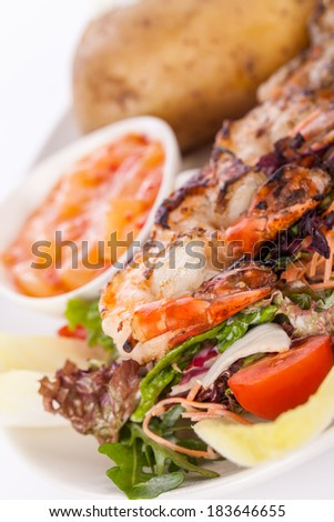 Grilled prawns with a green leafy lettuce and endive salad and a jacket potato topped with sour cream served on a white plate, close up high angle view on white