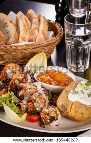 Grilled prawns with a green leafy lettuce and endive salad and a jacket potato topped with sour cream served on a white plate, close up high angle view on white - stock photo