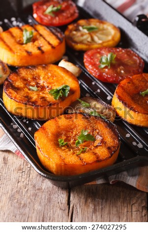 Grilled pumpkin and vegetables on the grill pan. Vertical macro, rustic style - stock photo