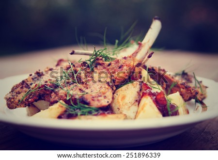 Grilled rack of lamb with fried potatoes and onion chutnee shot outdoors, toned image - stock photo