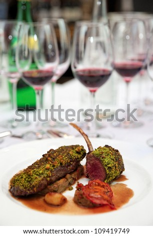 Grilled rack of lamb with mint and pistachio on arranged table