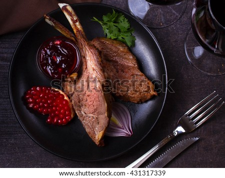 Grilled rack of lamb with pomegranate sauce in black plate on dark textural background. View from above, top studio shot