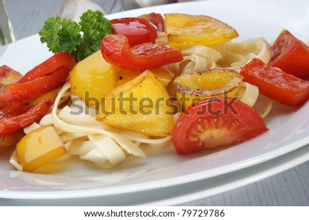 grilled red and yellow peppers with tomato on pasta