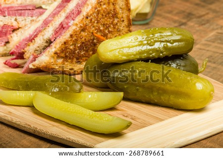 Grilled reuben sandwich with dill pickle spears - stock photo