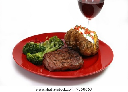 Grilled rib eye steak with baked potato and broccoli spears.  Isolated on white background. - stock photo