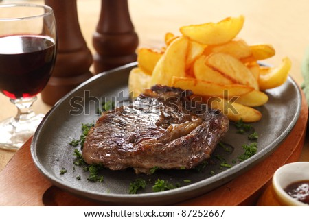 Grilled rib fillet steak with fried chips ready to serve.