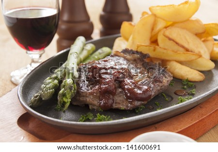 Grilled rib fillet steak with ketchup, asparagus and fried chips ready to serve.