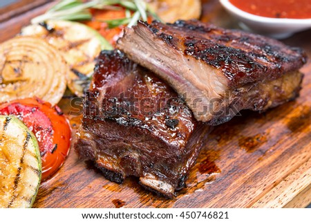 Grilled ribs with sauce on a wooden board with vegetables