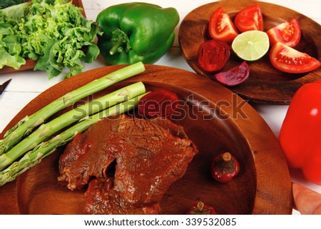 grilled roast red beef meat served on wooden dishes with peppers cutlery salad and vegetables on white wooden table - stock photo