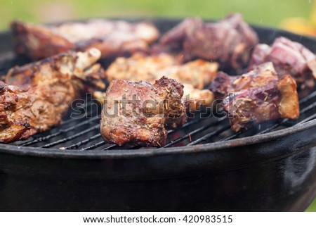 Grilled roasted juicy lamb steaks on cooking on barbecue, outside - stock photo