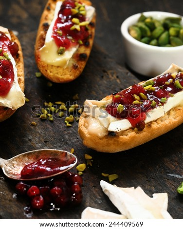 Grilled rolls topped with camembert cheese, chopped, pistachio nuts and cranberries in syrup for tasty tapas or appetizers - stock photo