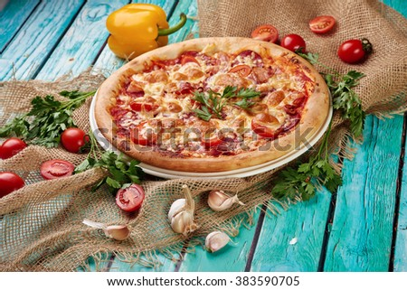 Grilled round pizza with cheese surrounded by red tomato next two sweet pepper yellow and red on a green wooden background - stock photo