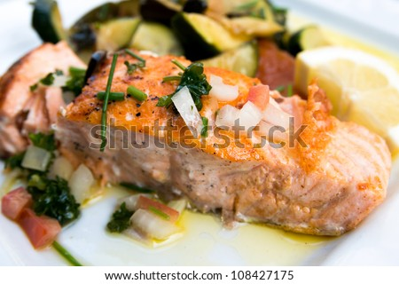 grilled salmon and lemon - french cuisine dish with tomato and salmon - stock photo