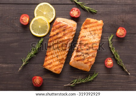 Grilled salmon and tomato, lemon, rosemary on the wooden background. - stock photo