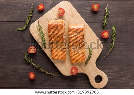Grilled salmon and tomato, rosemary on the wooden background. - stock photo